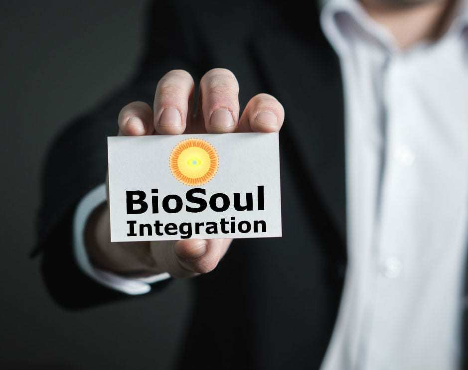 man holding up a BioSoul Integration business card