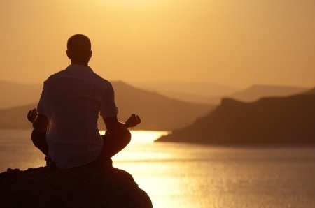 man sitting in mindfulness meditation doing shadow work in front of sunset