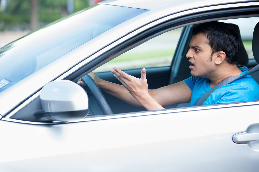 man in car with head jutting forward and angry look on face