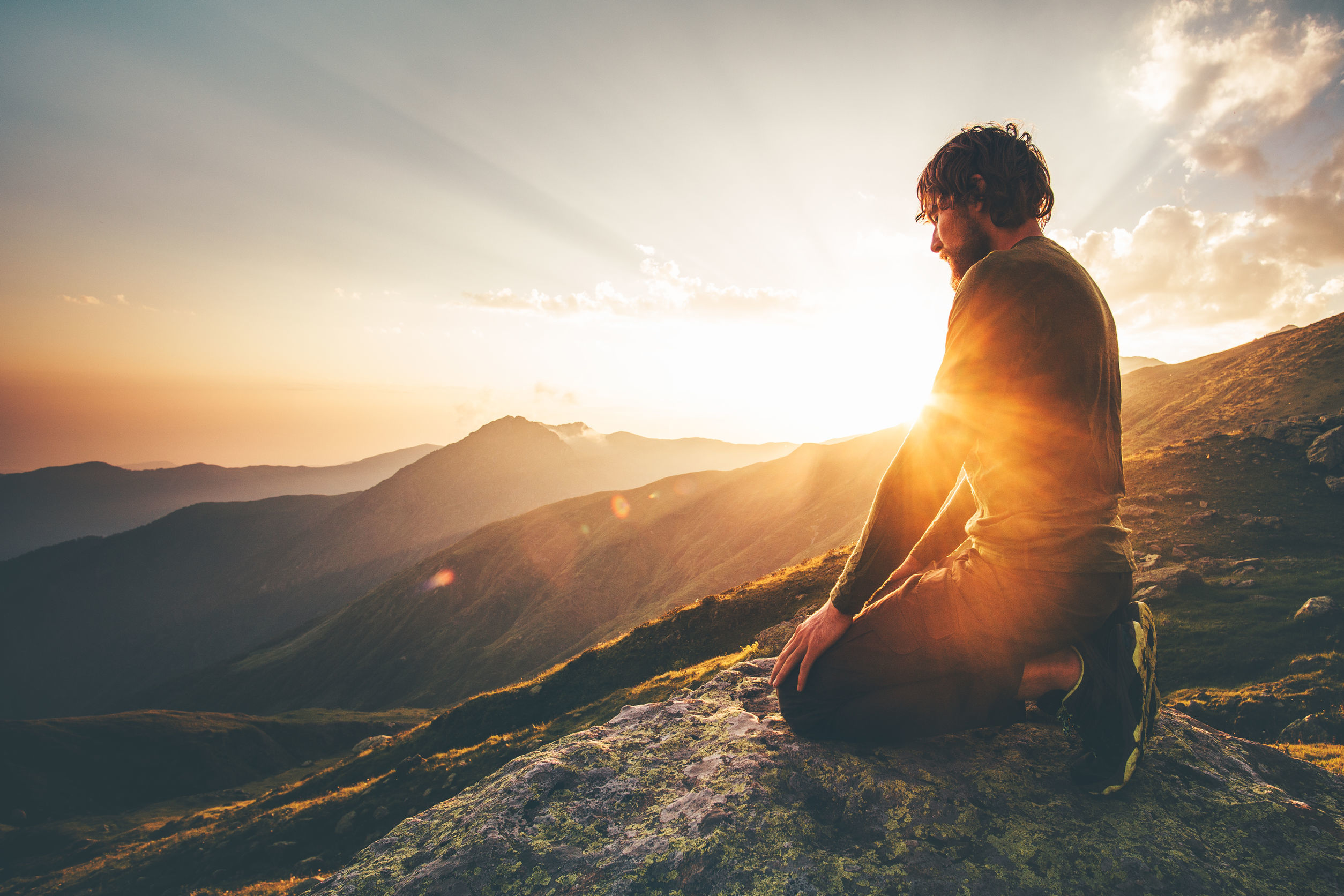 man sitting on mountain top in sun spiritual healing and entrainment
