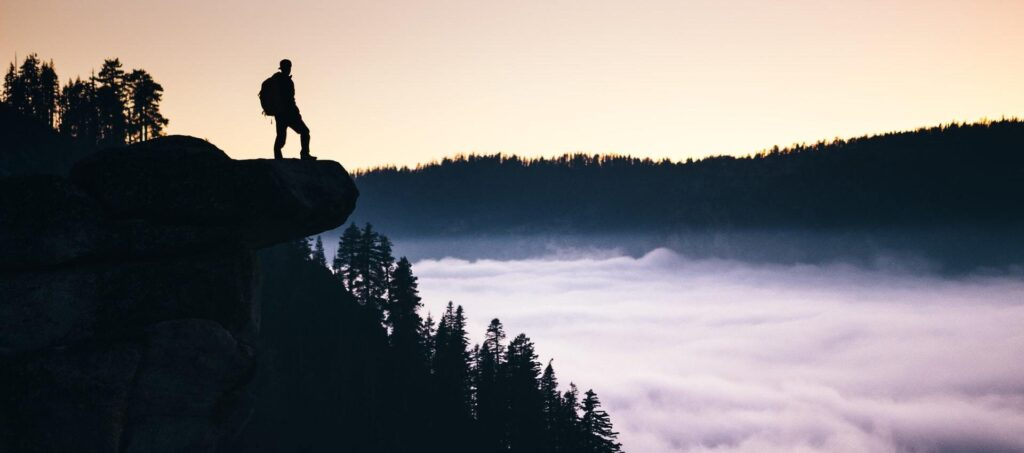 man standing at the edge of a cliff contemplating self improvement challenges