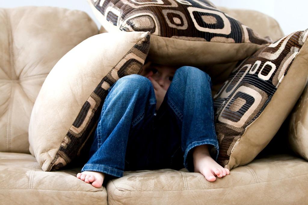 little boy hiding under the couch afraid
